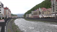 Mountain river at valley, modern small town, cloudy flow - stock footage
