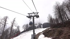 Approach steel aerial lift pylon, melting snow at mount slope Stock Footage