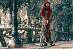 Young woman riding red vintage bike on fall season Stock Photos