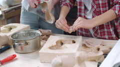 Tilt up of two young female artists making papier mache dog figures of craft  Stock Footage
