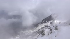 Aerial shot, snowy mountain landscape seen through semitransparent cloud Stock Footage