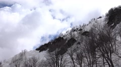 Bright cumulus clouds over dull snowy mountain slope, aerial view in motion Stock Footage