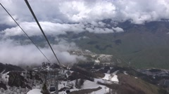 View from cable car ride down over high mountain peaks and canyon Stock Footage