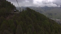 View from cable car gondola ride down over somber forested valley - stock footage