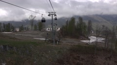 Panoramic view of ski resort in low season, slide above empty ground field Stock Footage