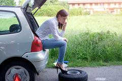 Sad woman calling assistance service  after unexpected vehicle breakdown Stock Photos