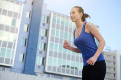 Sportive woman running outdoor in the city Stock Photos