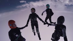 Parachutists holding hands in sky. Skydiving. Flight above green fields - stock footage
