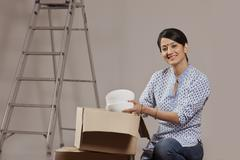 Young woman packing crockery Stock Photos