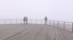 Few people at foggy observation deck, mount top, milklike air around Stock Footage