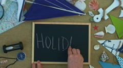 4k holiday composition with a hand writing word holiday on board Stock Footage