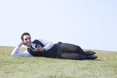 Portrait of businessman with mobile phone lying down , INDIA , DELHI Kuvituskuvat
