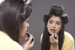 Young woman applying lipstick Kuvituskuvat