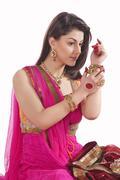 Woman adjusting bangles on wrist Stock Photos