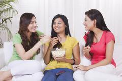 Young women eating pop corn Kuvituskuvat