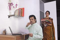 Man working on laptop and woman keeping clothes in cupboard Stock Photos