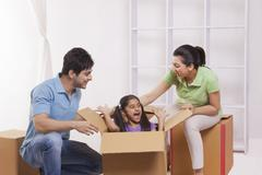 Girl playing hide and seek with parents Stock Photos