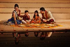 Family arranging diyas on rangoli Stock Photos
