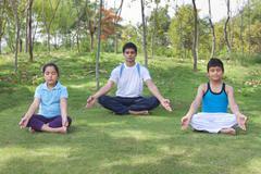 Family meditating outdoors Stock Photos