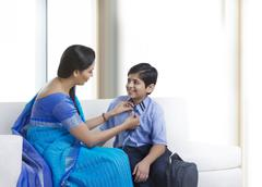 Mother helping son with neck tie Stock Photos