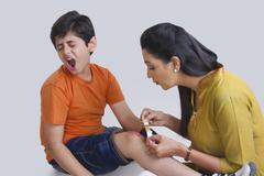 Mother putting bandage on sons wound Stock Photos