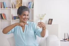 Portrait of old woman with glass of milk Stock Photos