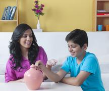 Brother and sister inserting a coin into a piggy bank Stock Photos