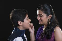 Sister feeding sweets to her brother at Bhaidooj Stock Photos
