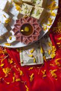 Top view of sweets , diya and currency Stock Photos
