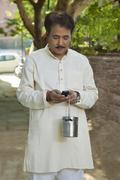 Man holding milk canister and using cell phone Stock Photos