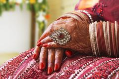 Close-up of a brides hands in wedding bangles and ring Stock Photos