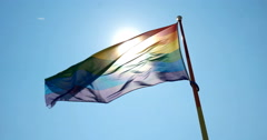 Colorful flag with sun shining through against blue sky - stock footage