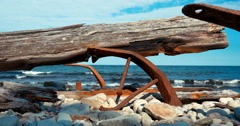 Detail of rusty iron and log on pebble beach against the sea Stock Footage