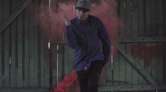 Active young male dancing on an old wooden door and red smoky background. - stock footage