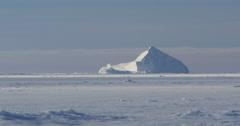 Sea birds circle and heat waves around distant massive iceberg Stock Footage