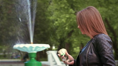 Slender girl goes along fountain with metal rose. Slow motion Stock Footage