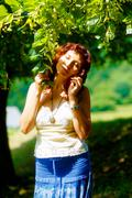 gentle prayer to a beautiful linden tree on bright midsummer day - stock photo