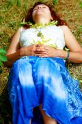 Dreaming girl lying on meadow sprinkled with linden tree flowers Stock Photos