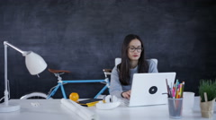 4K Thoughtful businesswoman working at her desk in creative office Stock Footage