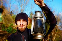 Young handsome man in sport outfit holding old lantern. Eye contact Stock Photos