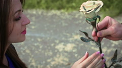 The stranger gives a young girl a metal rose. Close up Stock Footage