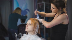 stylist hairdresser does a professional paint on the hair of his client - stock footage