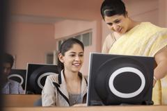 Teacher assisting student in classroom Stock Photos