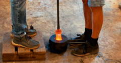 Glass blowing into a mould on the ground with two pairs of legs either side Stock Footage