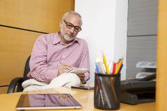 Senior executive writing in notepad Stock Photos