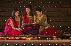 Friends arranging diyas Stock Photos