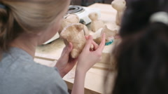 Over the shoulder close-up view of two young craftswomen making paper mache t Stock Footage