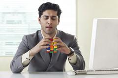 Businessman solving Rubik's Cube puzzle Stock Photos