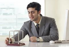 Businessman looking at a pendulum on office desk Stock Photos