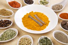 Assorted spices on spoons arranged around plate of turmeric and cinnamon Stock Photos